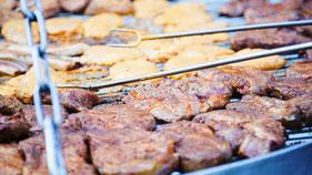 Ein Schwenkgrill mit Nackensteaks, Bauchspeck und Putenfleisch gegrillt auf Buchenholz.