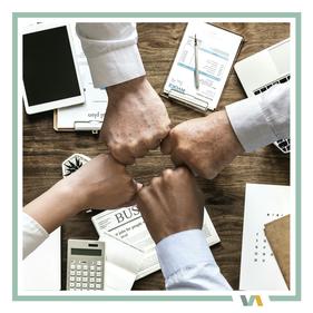 Virtuelle Assistenz Zusammenarbeit: mehrere Hände in der Mitte des Schreibtischs