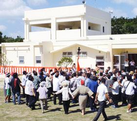 施設前で巻踊りを行い、喜ぶ島民ら出席者=28日午後、新城島上地島