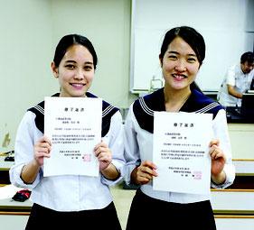 修了証書を手に笑顔を見せる渡嘉敷さん(写真左)と山田さん。医学部進学の夢を膨らませた=10日、琉球大学