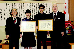 表彰状を見せる島尻くん(右から2人目)と瀬底さん(右から3人目)=22日、県議会議長室