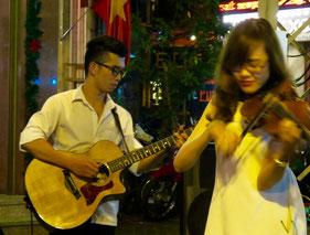 ein Gitarist, eine Geigerin und ein Trommler
