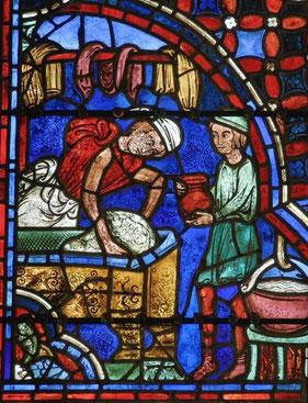 Un boulanger pétrit la pâte, dans laquelle on distingue le visage du Christ. Vitrail de Chartres. Baie des Apôtres.