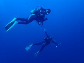 綺麗なマリンブルーの中を泳ぐダイバーの写真です。