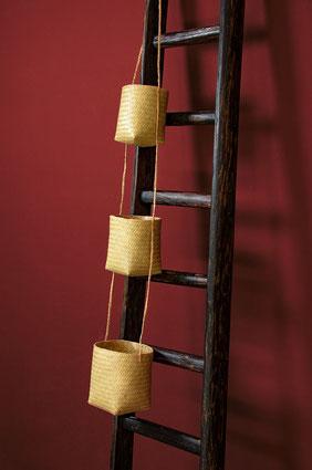 Cestini in paglia intrecciata per arredare con una scala a pioli in legno stile old factory