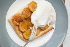 Aprikosenkuchen mit Sahne auf einem Teller.