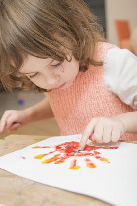 Kleinkind spielt mit Fingerfarben. Das Kind malt mit bunten Farben auf ein Blatt.