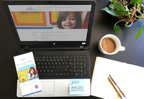 Aufsicht auf geöffneten Laptop, Notizblock, Kaffeetasse, KLIMAfuchsflyer