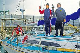 肌寒い風を受け、「安全航海で行ってきます」と元気に出港する前田船長(左端)と高校生=石垣港、午前10時過ぎ