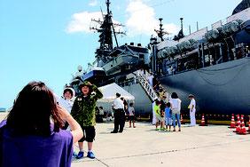 艦内見学を終えた後、ブースの制服を身に着け、護衛艦を背に写真を取る人は多かった。自衛官と一緒にわが子の写真を撮る親の姿もあった=2日、中城港湾の新港地区
