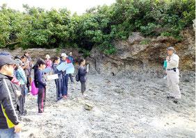 真栄里海岸に残る銃眼の跡(中央奥)を巡る児童生徒