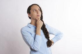 Frau fasst sich skeptisch fragend mit der Hand ans Kinn
