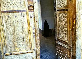 Frau betet in der Moschee hinter der halb geöffneten Tür