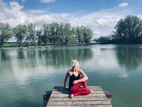 Yogalehrerin und Achtsamkeitslehrerin Natascha Königsbauer in der Natur bei ihrer yogapraxis für mehr Selbstfürsorge im Alltag.
