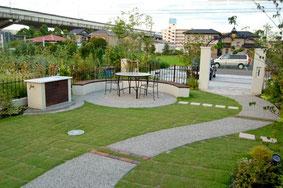 庭は曲線のアプローチにあわせた円形のベンチで