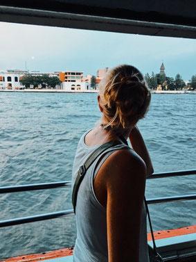 Frau guckt vom Boot aus auf den Fluß in Bangkok