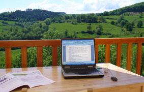 Ordianteur sur une terrasse face à la nature