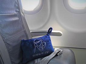 Ein dunkelblaues Kissen liegt auf einem Flugzeugstuhl.