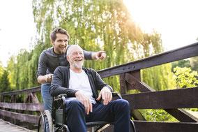 Junger Mann schiebt Senior im Rollstuhl - Pflegedienst Silke Stecker