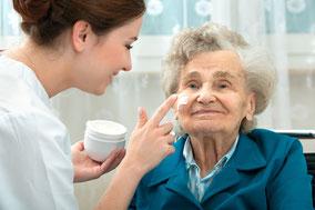 Pflegefachkraft cremt Seniorin das Gesicht ein - Ambulante Behandlungspflege