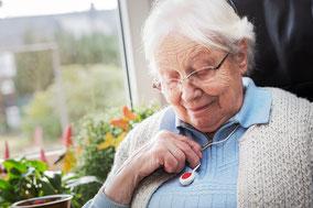 Seniorin mit Notfallknopf - Hausnotruf