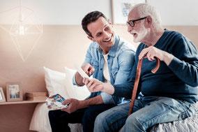 Junger Mann unterhält sich mit Senior - Besondere Betreuung nach §45