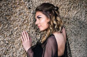 Model im Profil in einem schwarzen langen Abendkleid