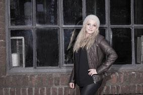 Blonde Frau mit Dauerwelle vor einem Fenster
