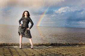 Modelfoto bei Sonne, Wolken und Regenbogen