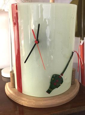 Horloge demi cercle sur socle en bois.         Prix : 129€