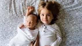 Zwei kleine Kinder auf einem Bett liegend.