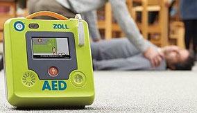 Defibrillator (AED) am Boden und bewusstlose Person sowie Ersthelfer im Hintergrund