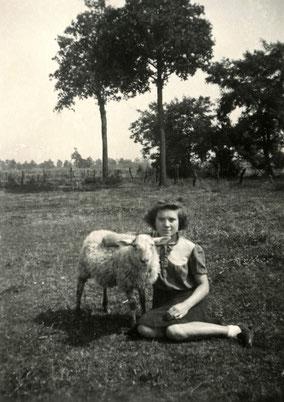 Meisje zittend in een weide met één schaap. Zwart-wit foto.