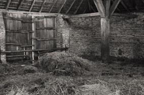Oude schuur met vers hooi en stro. Zwart-wit foto.