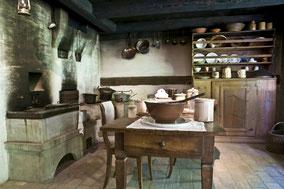 Keuken van een oude hoeve met tafel, stoelen, kast en oven. Kleurfoto.
