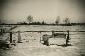 Vlak sneeuwlandschap met waterput en weide met omheining. Zwart-wit foto.