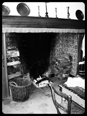 Oude open haard met houtblokken en rieten mand. Zwart-wit foto.