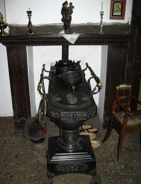Zwarte oude kachel met een houten stoel en twee paar houten klompen