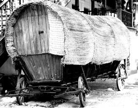 Oude paardenwagen met overkapping. Zwart-wit foto.
