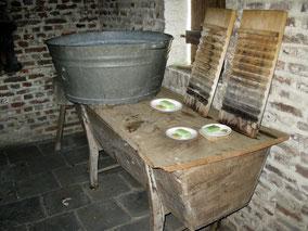 Zinken wastobbe op een houten tafel met groene zeep. Twee wasborden. Kleurfoto.