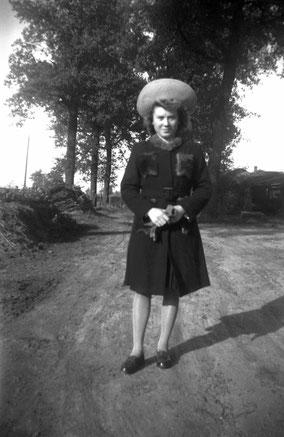 Zwart-wit foto. Bomenlaan met een vrouw met wintermantel, handschoenen en grote hoed.
