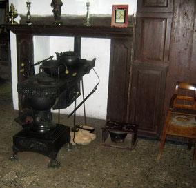 Zwarte oude kachel met houten schouwmantel; Een stoel en twee paar houten klompen. Kleurfoto.