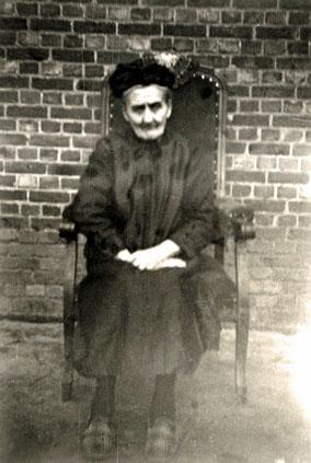 Regina Theys in het zwart gekleed als oude vrouw in een zetel. Zwart-wit foto;