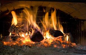 Een open vuur. Bakoven met brandend hout. Kleurfoto.
