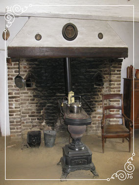 Oude kolen en houtkachel met een waterketel. Een stenen schouw.