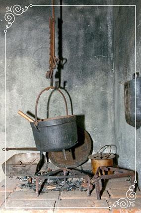 Koperen ketel hangend aan een ketting. Onderaan  een uitgedoofd houten vuur.