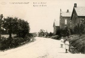Oude foto met schoolgebouwen, een weg en twee kinderen. Zwart-wit foto.
