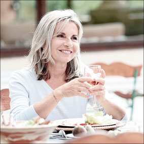 Frau mit Weinglas bei gutem Essen