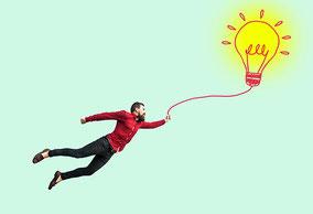 Mann fühlt sich leicht, er fliegt und hält eine gezeichnete Glühbirne an einer Leine. Leichtigkeit und Kreativität durch Wingwave.