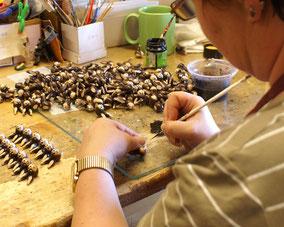 Kunsthandwerkerin beim Bemalen von Firuren